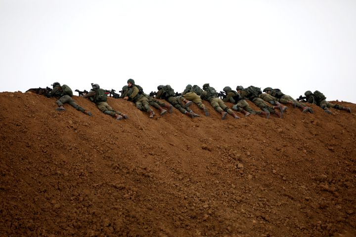 Israeli soldiers are perched atop a dune on the Israeli side of the border with the northern Gaza Strip on Friday.