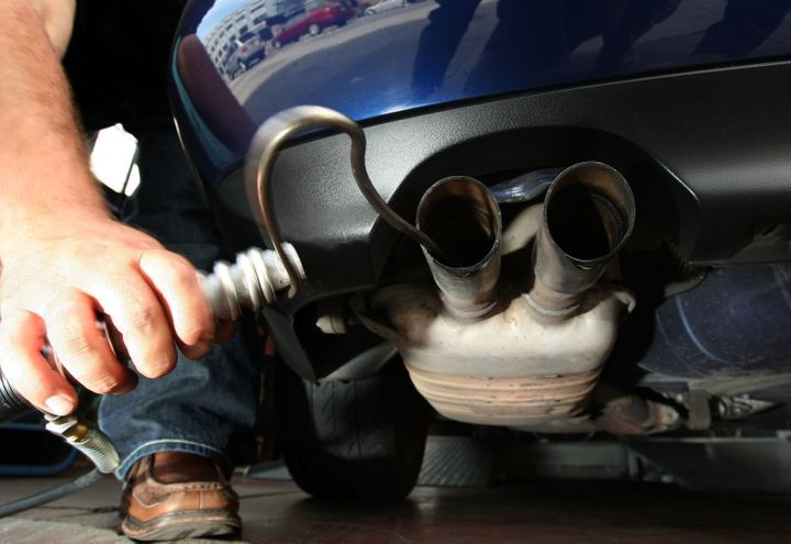 A man in California inserts a probe into the tailpipe of a car while performing an emission test.