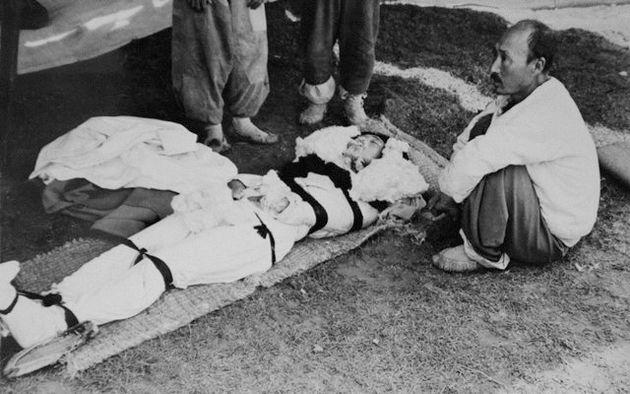 """처참하게 살해된 여성의 주검. 옆에 가족인 듯 보이는 노인이 멍한 눈으로 정면을 보고 있다. 미군은 """"공산군 빨치산에 의해 살해된 주검과 그들의 친지 및 친구들""""이란..."""