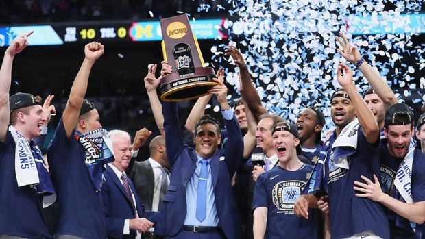 SAN ANTONIO, TX - APRIL 02:  Head coach Jay Wright of the Villanova Wildcats raises the trophy with his team after defeating the Michigan Wolverines during the 2018 NCAA Men's Final Four National Championship game at the Alamodome on April 2, 2018 in San Antonio, Texas.  Villanova defeated Michigan 79-62.  (Photo by Tom Pennington/Getty Images)