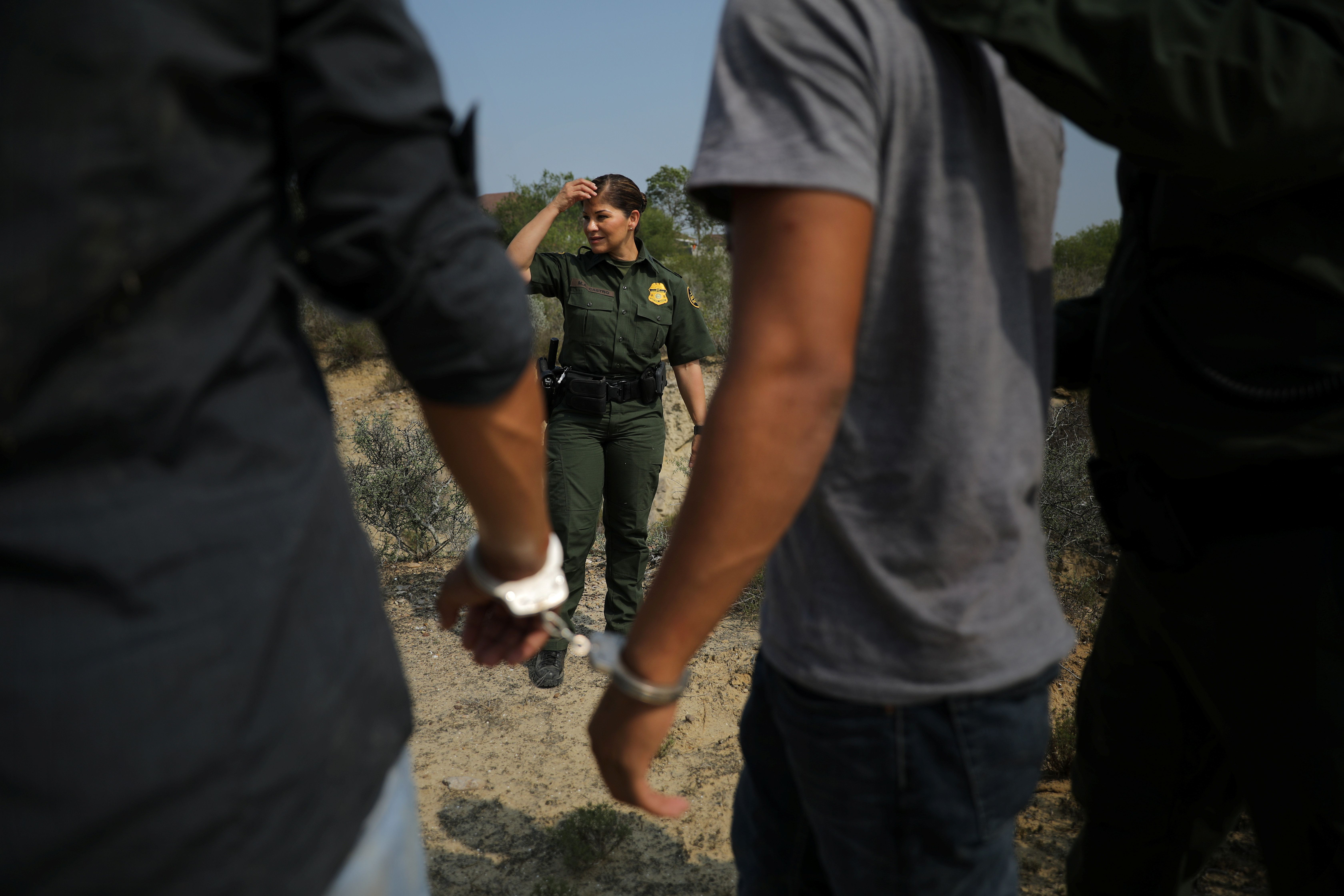 "A U.S. border patrol agent stands next to men being detained after entering the United States by crossing the Rio Grande river from Mexico, in Roma, Texas, U.S., May 11, 2017. REUTERS/Carlos Barria           SEARCH ""BARRIA BORDER"" FOR THIS STORY. SEARCH ""WIDER IMAGE"" FOR ALL STORIES."