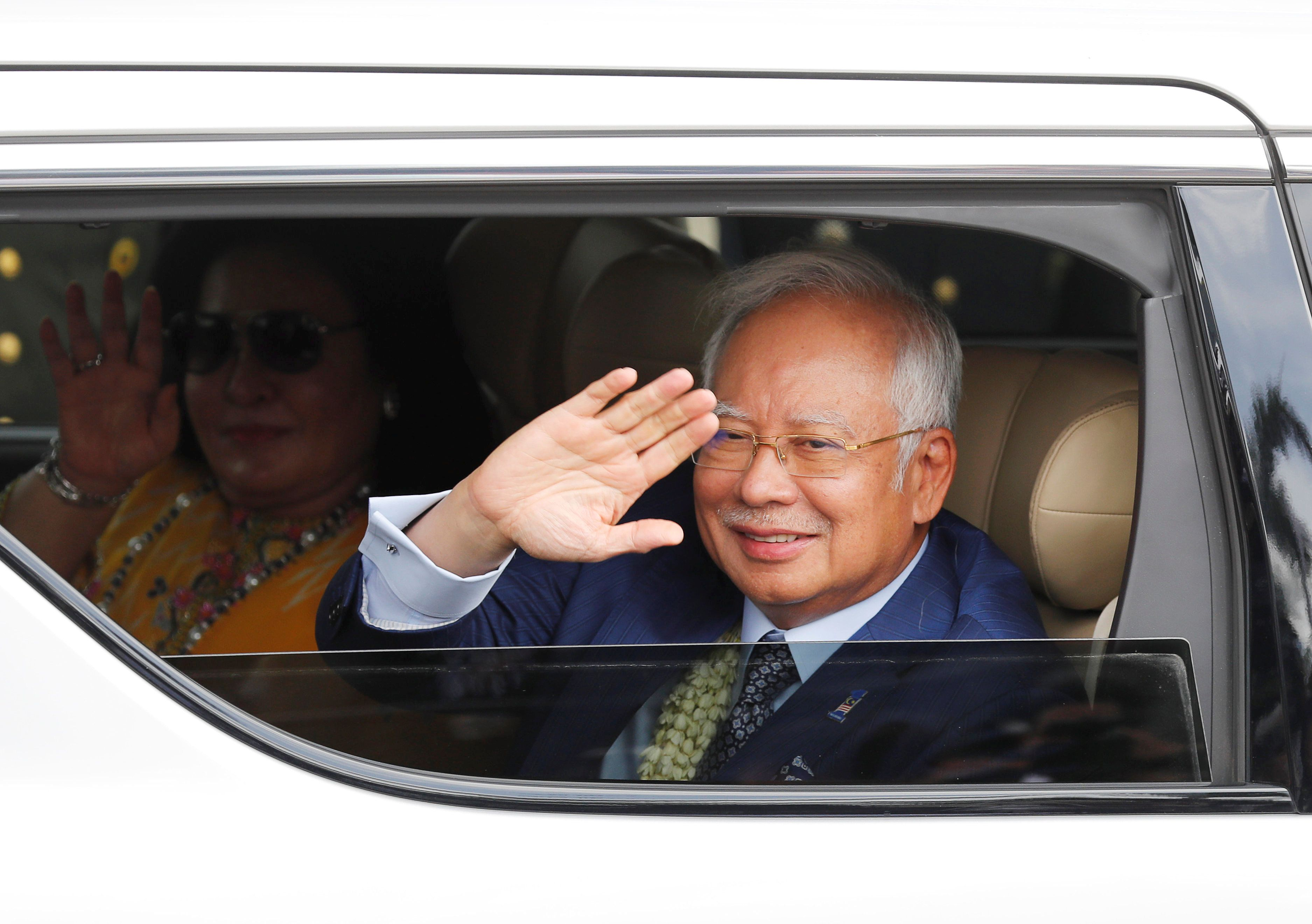 Malaysian Prime Minister Najib Razak and wife Rosmah wave to the crowd upon their arrival to attend the Association of Southe