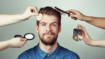 Studio portrait of a young man getting a makeover against a gray background