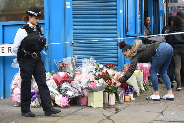 A woman lays flowers on Chalgrove Road, Tottenham, north London, where a 17-year-old girl has died after...