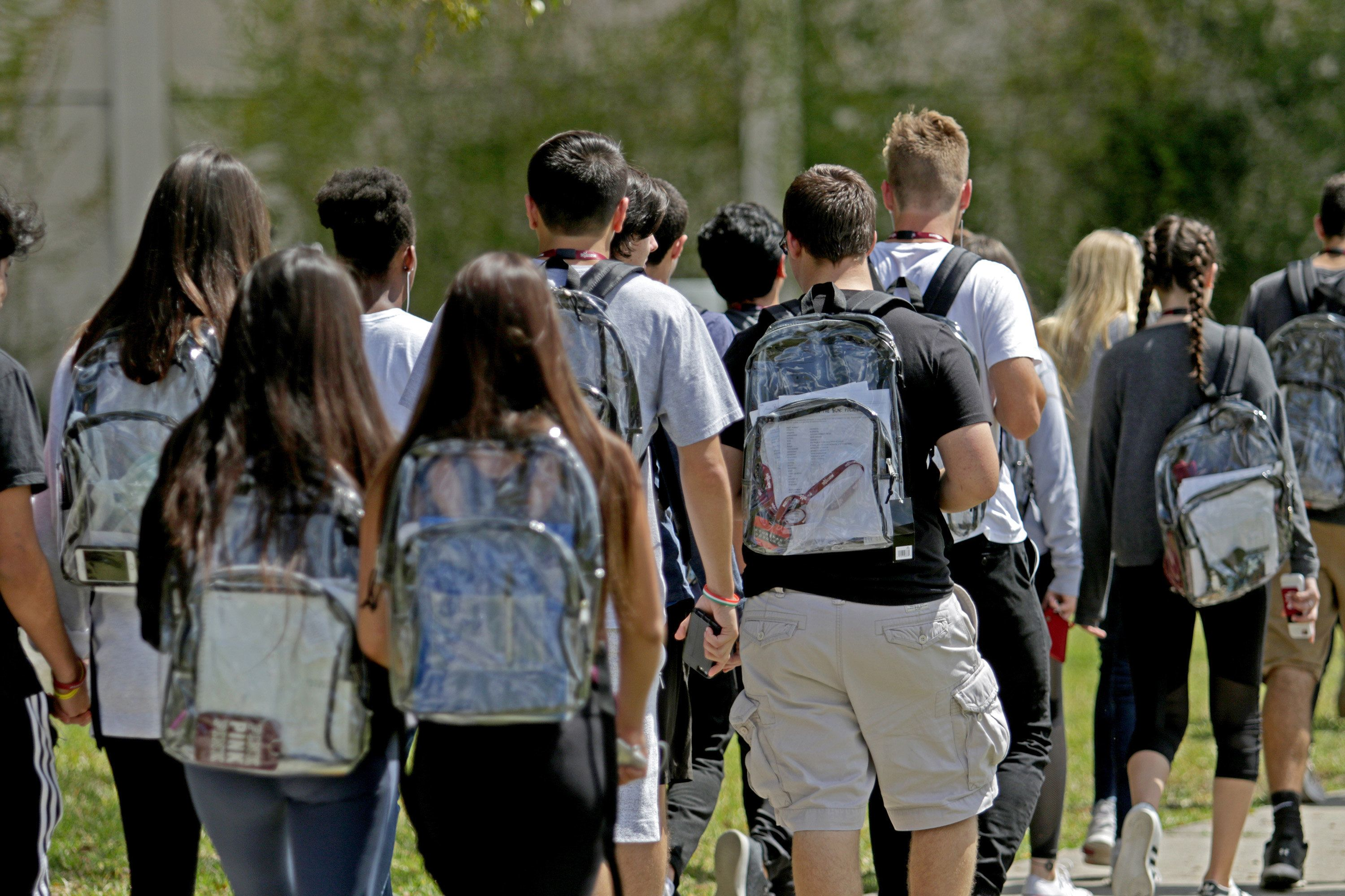 Students wear clear backpacks outside of Marjory Stoneman Douglas High School in Parkland, Fla. on Monday, April 2, 2018. Extra security is one of a number of security measures the school district has enacted as a result of the Feb. 14 shooting at the school that killed 17. (John McCall/Sun Sentinel/TNS via Getty Images)