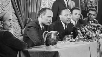 (Original Caption) 1/7/1966-Chicago, IL: Doctor Martin Luther King (C) announces at a news conference what he terms a 'freedom' movement to be launched in Chicago. King told the conference the campaign will be 'the first significant northern freedom movement aver attempted by major civil rights forces.' At left is Al Raby, Chicago civil rights leader. At right is Andrew Young of Atlanta.