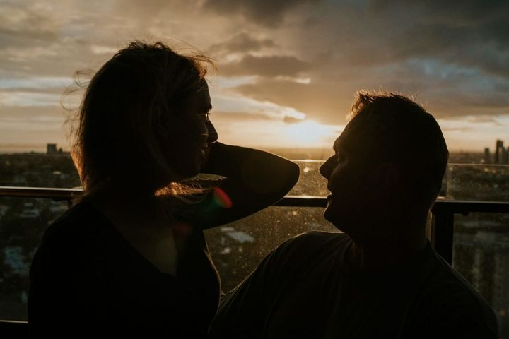 Agnew and her fiancé, Rob Campbell, are on the balcony of their apartment with the sun setting behind them. She sits on his lap as he holds her hair back from her face with one hand.