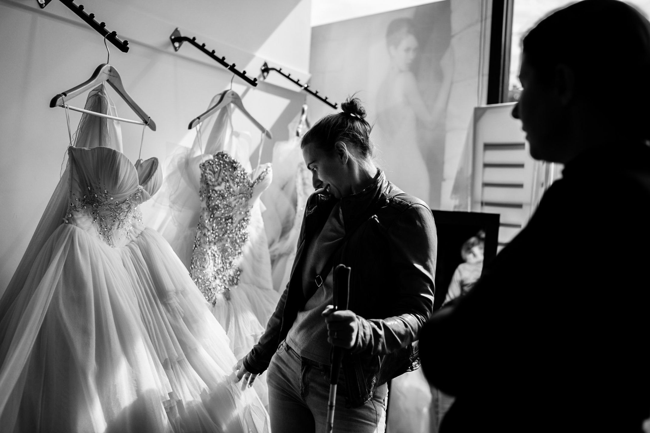 Steph Agnew touches a wedding gown that's been brought out for her to examine while her friend and bridesmaidJess,...