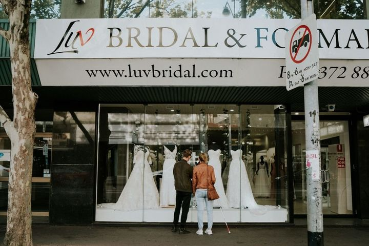 Agnew, who is using her cane, and her brother Cal gaze into the window of the bridal shop where four white gowns are displaye