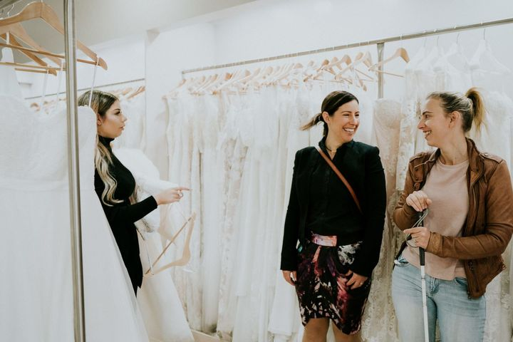 A salesperson, at left, holds a wedding gown in her arms. To the right, Agnew and her friend Jess smile at each other as they're surrounded by racks of white dresses.
