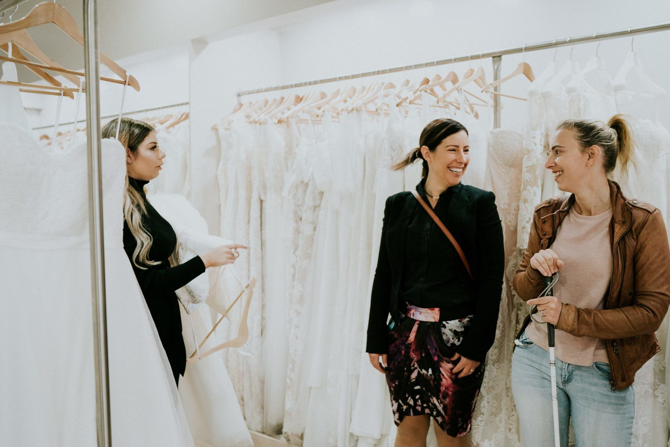 A salesperson, at left, holds a wedding gown in her arms. To the right, Agnew and her friend Jess smile at each other as