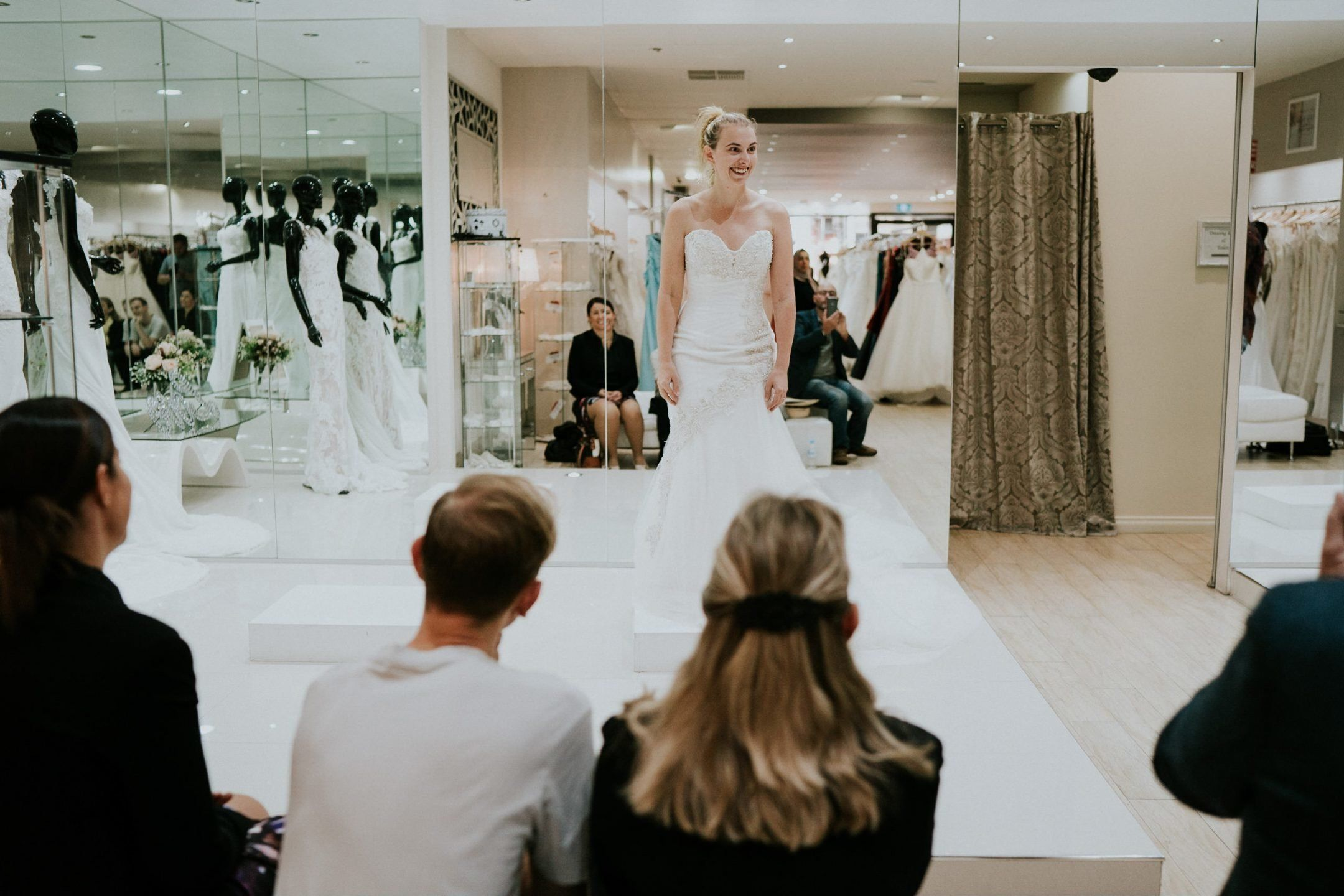 Steph Agnew smiles brightly as she wears a white strapless gown on a small platform in the bridal shop. In the foreground are the backs of her entourage.