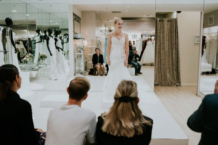 Steph Agnew smiles brightly as shewears a white strapless gown on a small platform in the bridal shop. In the foregroun