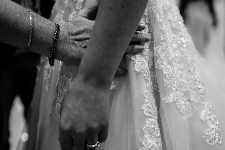 In this close-up image, Agnew's mother runs her hands along her daughter's hip as she gets a feel for how the beaded and embroidered wedding dress fits Steph.