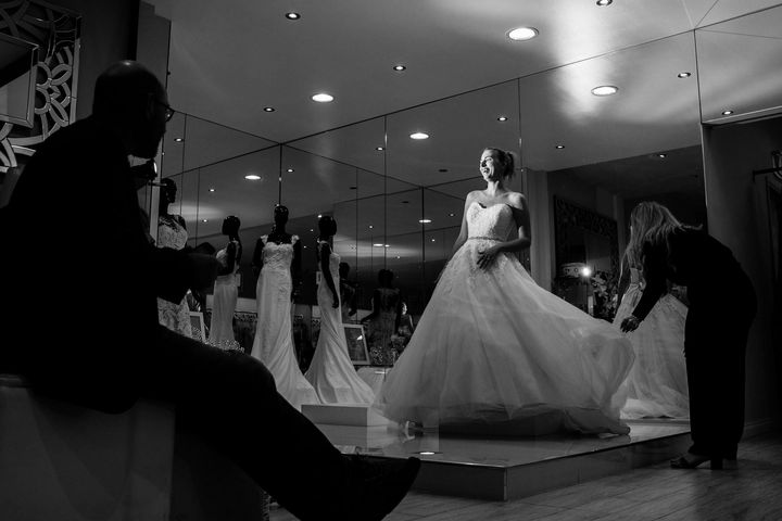 A smiling Steph Agnew stands atop a small platform wearing a flowy, strapless wedding gown. Her dad, who is in shadow on the left, watches his daughter. On the right, a bridal consultant straightens the hem of the gown.