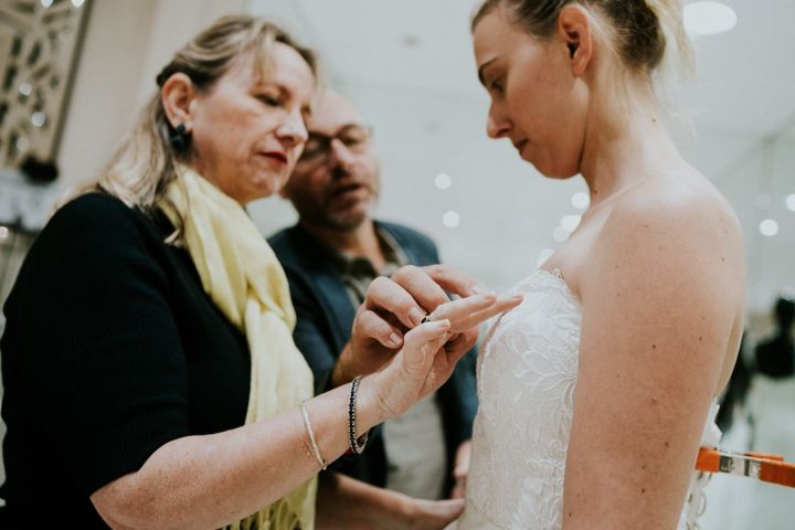 Agnew's father guides his wife's hand to the detailing on the embroidered bodice of a gown their daughter is trying on.