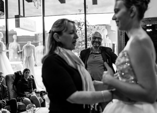 Agnew's mom touches the bodice of the beaded wedding dress her daughter has tried on. The father of the...