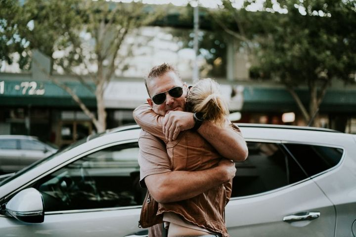 Campbell and Agnew hug outside of the bridal shop, where he dropped off her and her family for their appointment. Campbell, facing the camera and wearing aviator sunglasses, has his back to the bridal shop.