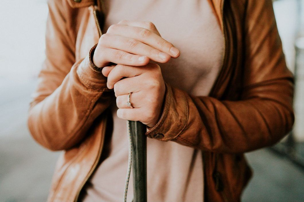 Agnew is shown in a close-up with her right hand atop her cane with her left hand, adorned with her engagement ring, below it