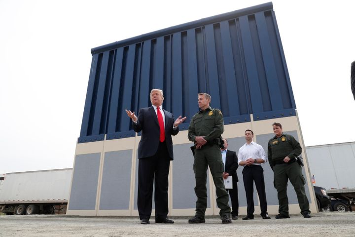 President Donald Trump stands with a Customs and Border Protection agent in front of a border wall prototype while visiting S