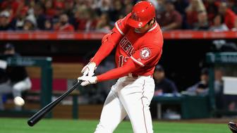 ANAHEIM, CA - APRIL 03:  Shohei Ohtani #17 of the Los Angeles Angels of Anaheim hits a three-run homerun during the first inning of a game as Roberto Perez #55 of the Cleveland Indians and umpire Jim Reynolds  look on at Angel Stadium on April 3, 2018 in Anaheim, California.  (Photo by Sean M. Haffey/Getty Images)