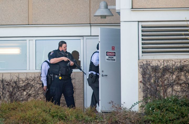 Police search a building at YouTube's corporate headquarters.