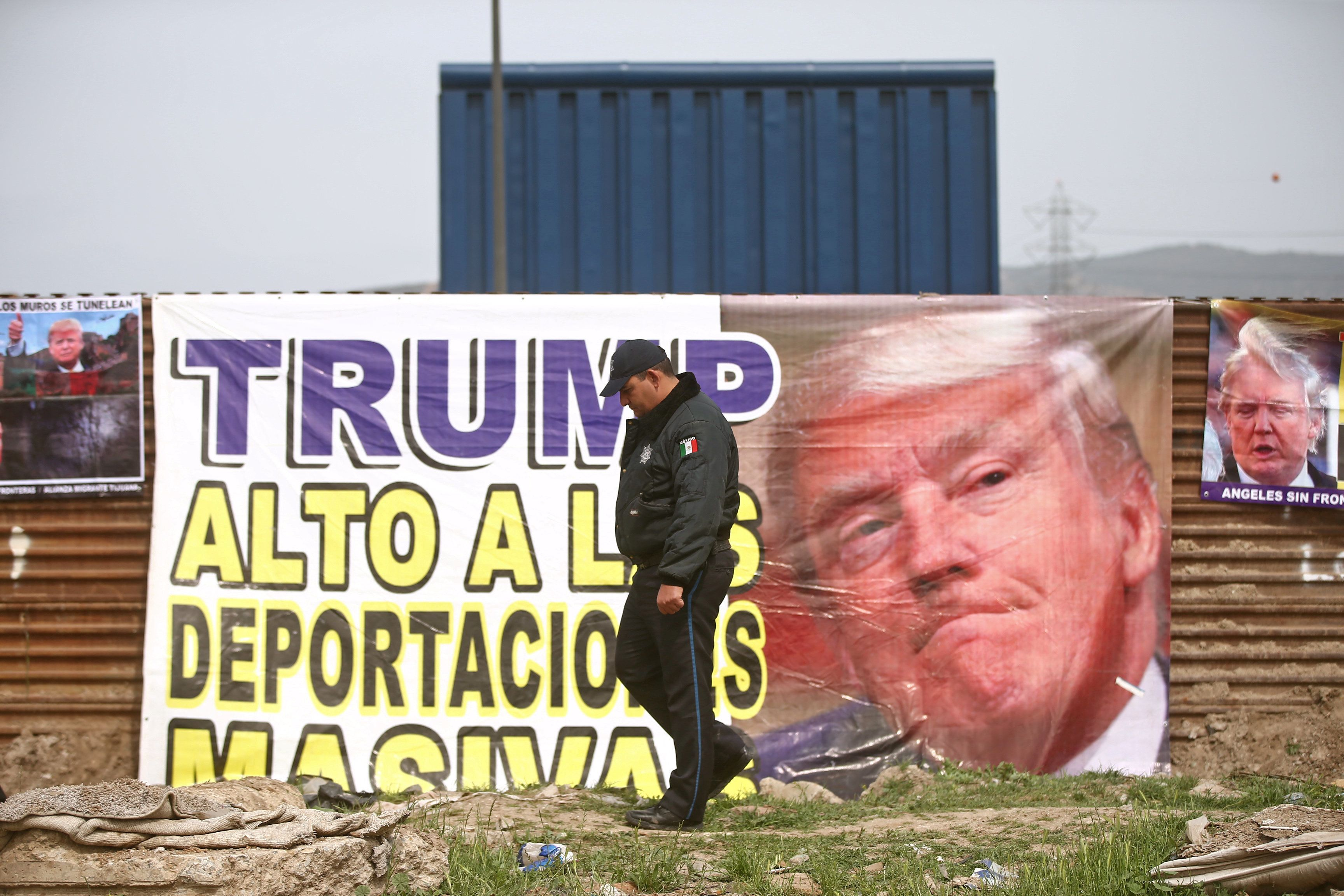"A Mexican federal police officer walks past a sign reading ""Trump, stop mass deportations"" and attached to the current border fence, near a prototype of U.S. President Donald Trump's border wall, in Tijuana, Mexico March 13, 2018. REUTERS/Edgard Garrido"
