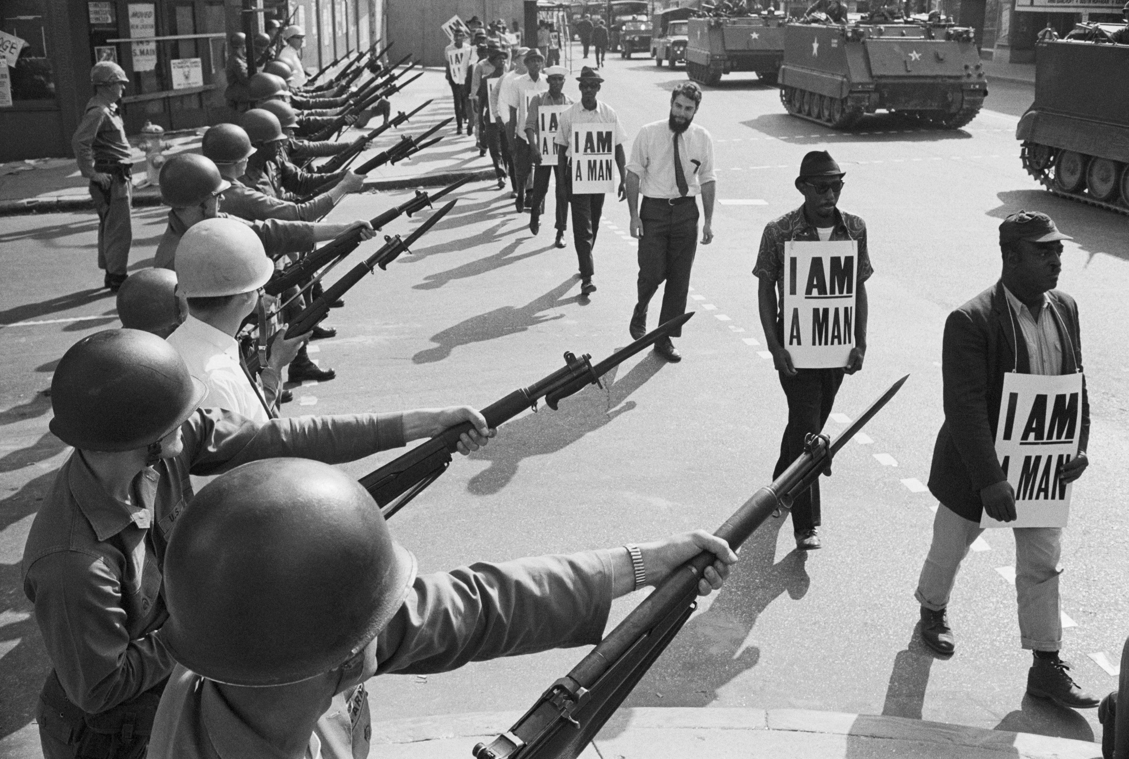 U.S. National Guard troops block off Beale Street as Civil Rights marchers wearing placards reading, 'I AM A MAN' pass by on March 29, 1968. It was the third consecutive march held by the group in as many days. Rev. Martin Luther King, Jr., who had left town after the first march, would soon return and be assassinated.
