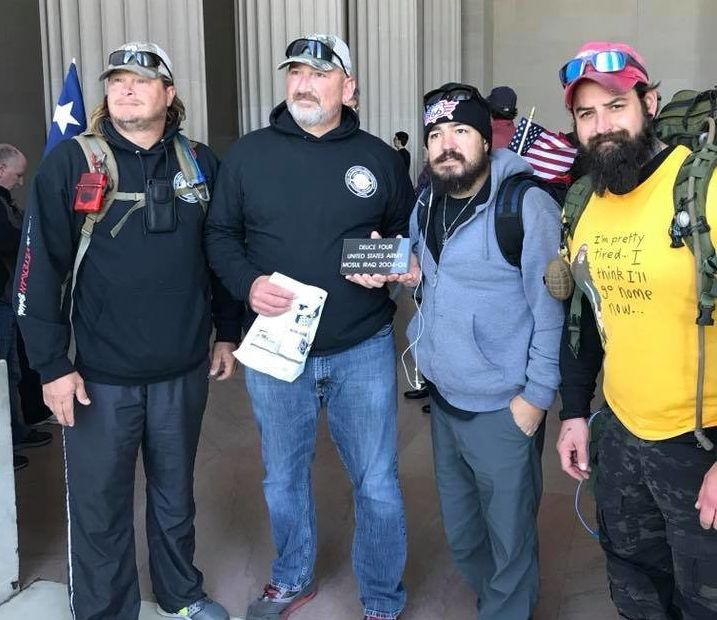 """From right, Adam Lingo and Eddie Montoya pose for a photo with fellow Deuce-Four veterans at the end of their """"Walk of Life"""" in Washington D.C. The veterans are holding a stone, inscribed with their infantry unit, that was set to be placed in a wall at the Department of Veteran Affairs."""