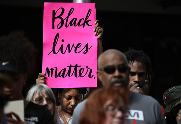 "A woman holds a bright ""Black Lives Matter"" sign during the demonstration."