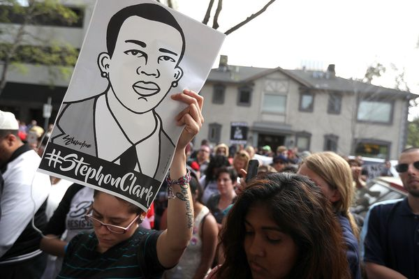 A woman holds a sign with an illustration of Clark.