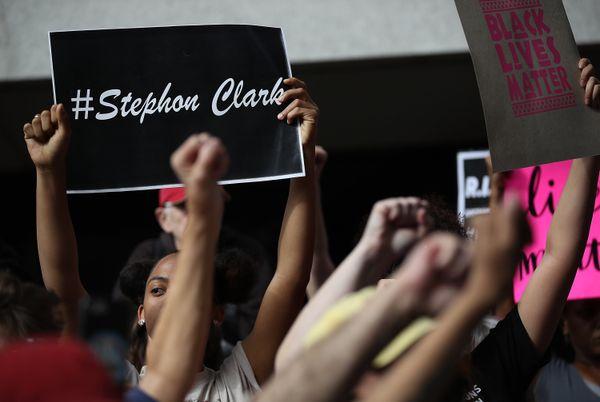Black Lives Matter activists raise their fists for Stephon Clark.