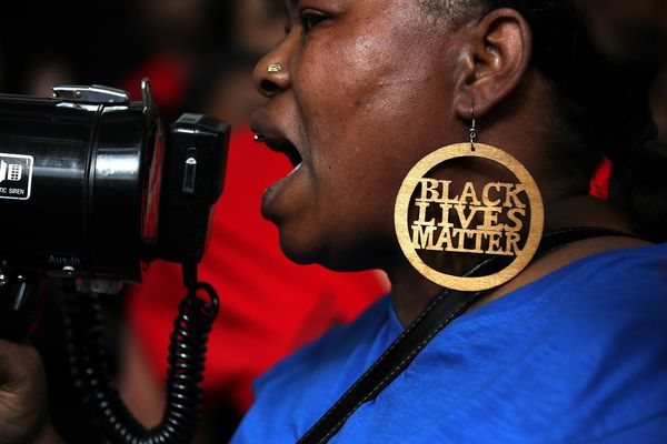 A Black Lives Matter protester uses a bullhorn during a demonstration in front of the offices of District Attorney Anne Marie