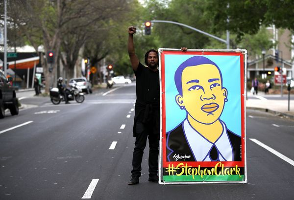 A Black Lives Matter protester holds an illustration of Stephon Clark.
