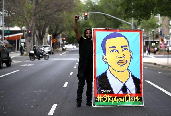 A Black Lives Matter protester holds an illustration of Stephon Clark.