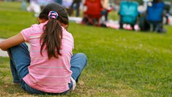 Young girl sits alone while her family and friends are enjoying a picnic together on Easter Sunday, but could be Memorial Day, Fourth of July, etc.