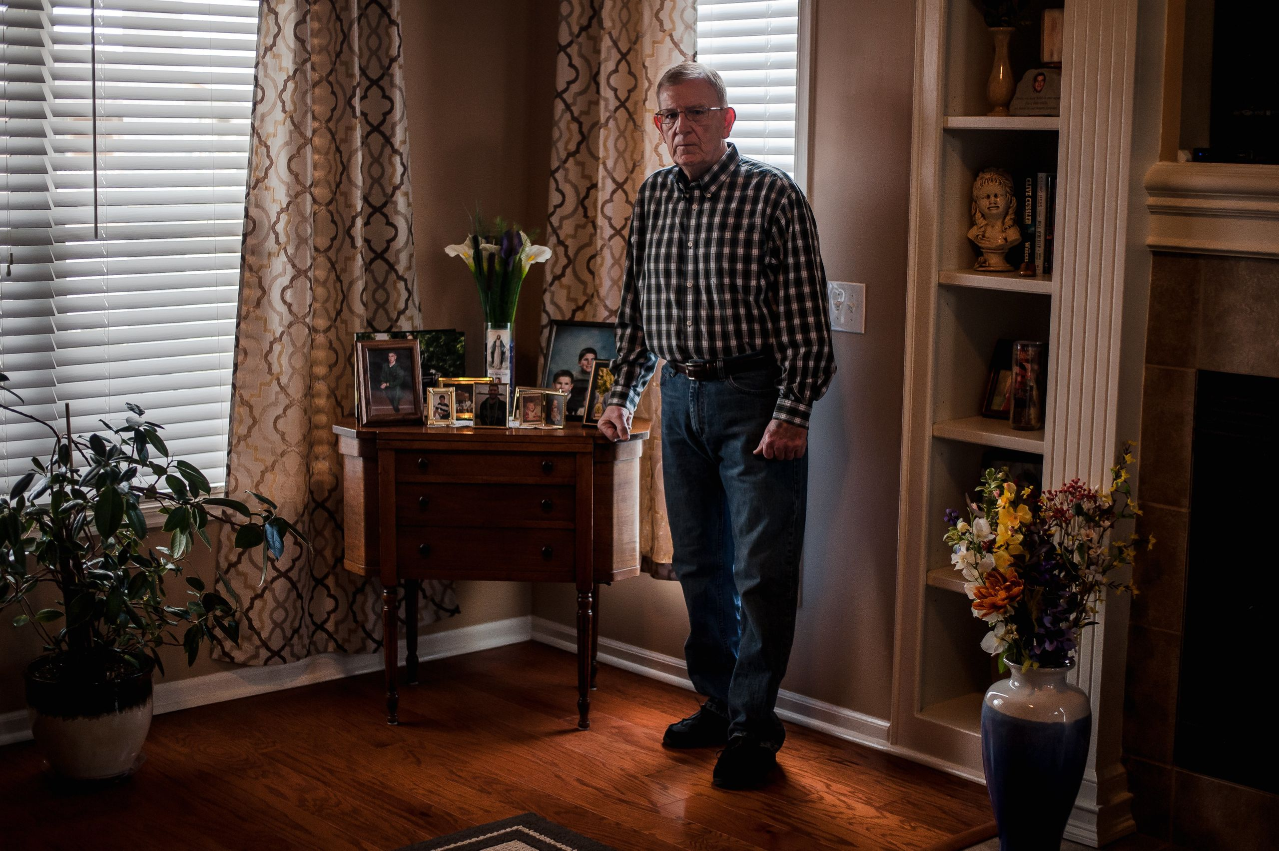 Bob Arthur in his Missouri home next to a memorial for his son Shawn Arthur.