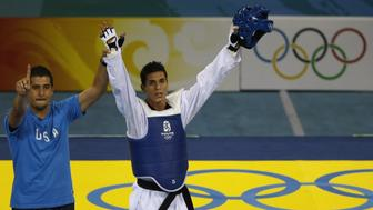 US coach Jean Lopez rises hand of his brother Steven Lopez after he defeated Rashad Ahmadov of Azerbaijan during the bronze medal contest of the men's -80 kg taekwondo match of the 2008 Beijing Olympic Games on August 22, 2008 in Beijing. Lopez won the bronze medal.  AFP PHOTO/BEHROUZ MEHRI       (Photo credit should read BEHROUZ MEHRI/AFP/Getty Images)