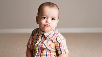 Baby/Toddler in plaid puckers his lips being silly while posing for the camera.