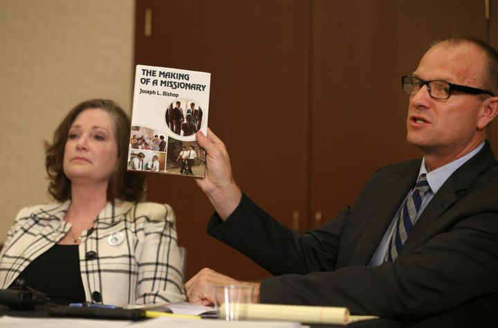 Attorney Craig Vernon holds up a book by Joseph L. Bishop at a news conference on April 5, 2018, in Salt Lake City.