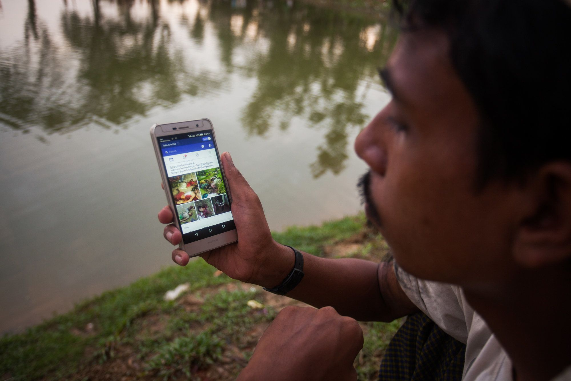 A Rohingya ethnic minority man looking facebook at his cell phone at a temporary makeshift camp after crossing over from Myanmar into the Bangladesh side of the border, near Cox's Bazar's Palangkhali, Friday, Sept. 8, 2017. Tens of thousands more people have crossed by boat and on foot into Bangladesh in the last two weeks as they flee violence in western Myanmar. (Photo by Ahmed Salahuddin/NurPhoto via Getty Images)