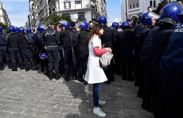 Une résidente en médecine entourée de policiers lors d'un rassemblement de protestation...