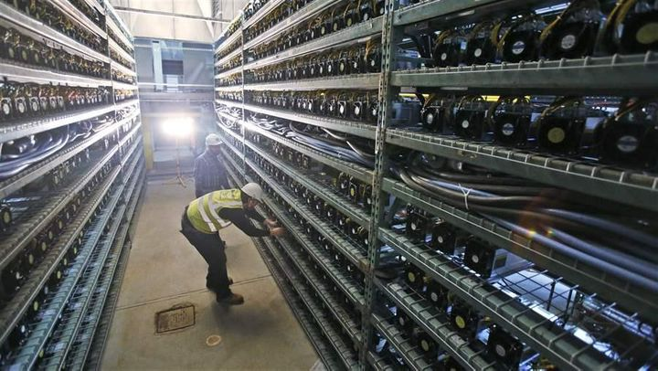 Workers look over racks of bitcoin data miners during construction of a bitcoin data center in Virginia Beach, Virginia. Whil