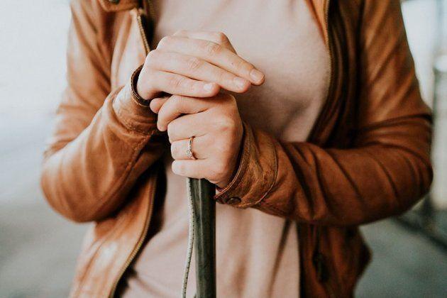 Eine Nahaufnahme von Agnew, die ihre rechte Hand auf ihreGehhilfe gelegt hat. Mit ihrer linken Hand hält...