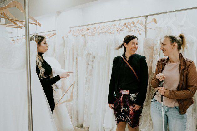 Eine Verkäuferin hält ein Kleid in ihren Armen. Auf der rechten Seitelächeln sich Agnew...