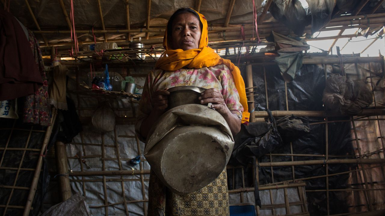 Anwar Beguma shows a water pot smashed by an elephant that trampled her family's house in Kutupalong refugee camp in Bangladesh. Her husband, Yakub Ali, died in the incident.