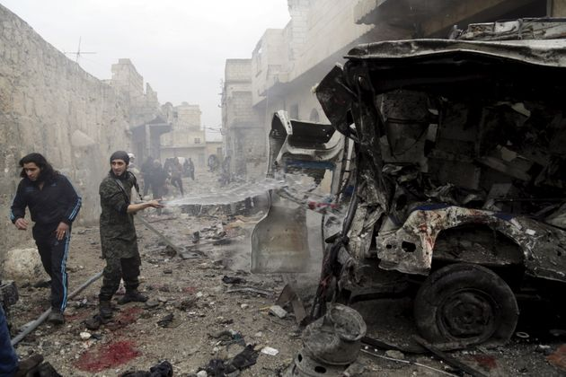A man sprays water on an ambulance at a site hit by what activists said were three consecutive air strikes...