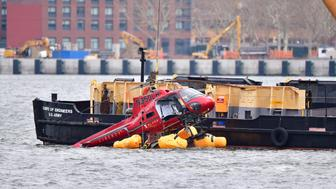 NEW YORK, NY - MARCH 12:  A helicopter is pulled from the East River on March 12, 2018 in New York City. Five people died after the helicopter made an emergency landing and flipped upside down on Sunday night, trapping the passengers inside.  (Photo by James Devaney/Getty Images)