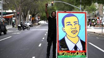 SACRAMENTO, CA - APRIL 04:  A Black Lives Matter protester holds an illustration of Stephon Clark during a march and demonstration through the streets of Sacramento on April 4, 2018 in Sacramento, California. Over 100 Black Lives Matter protesters rallied during a day of action outside of the Sacramento district attorney office demanding justice for Stephon Clark, an unarmed black man who was shot and killed by Sacramento police on March 18.  (Photo by Justin Sullivan/Getty Images)
