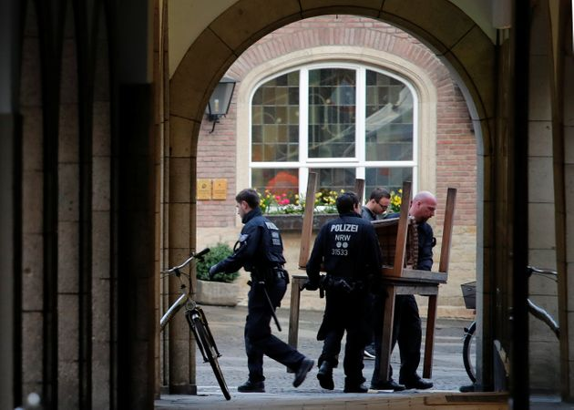 Police carry restaurant tables in front of the traditional guesthouse 'Grosser Kiepenkerl', where a man...